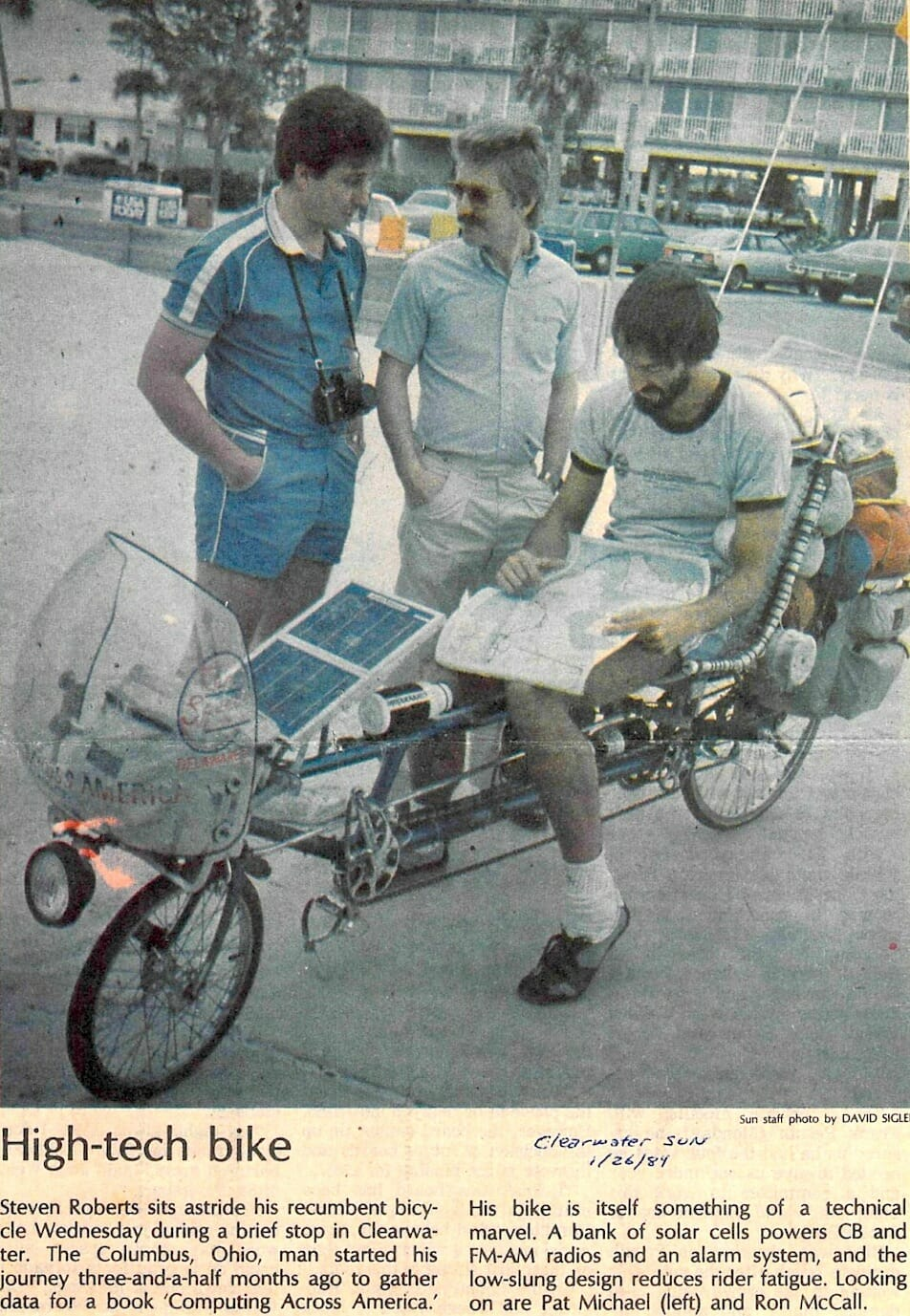 News clipping showing three men in 1984 around a solar-augmented reclining cycle